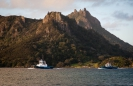 Tug boats returning to Marsden Point wharf with Mt Manaia across the harbour.